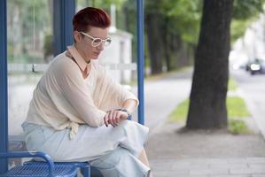 Frau sitzt an der Bushaltestelle und wartet foto