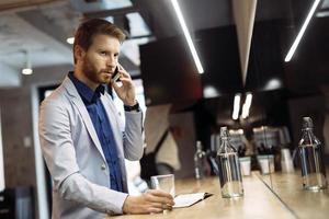 vielbeschäftigter Geschäftsmann, der am Telefon spricht