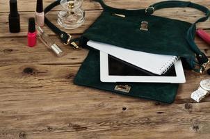 Wildledertasche mit Tablet, Notizblöcken, weißer Uhr und Kosmetik foto