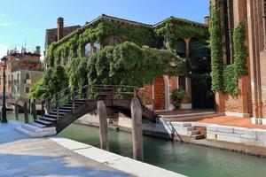 dunkelbraune Holzbrücke über den Kanal in Venedig, Italien foto