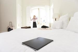 Laptop auf dem Bett, Frau, die durch Fenster im Hintergrund steht foto
