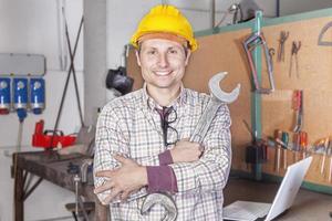 Porträt junger Metallarbeiterarme mit Schraubenschlüssel gefaltet