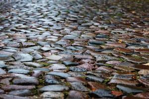 nasses Kopfsteinpflaster in einer mittelalterlichen Straße, Hintergrundbeschaffenheit foto
