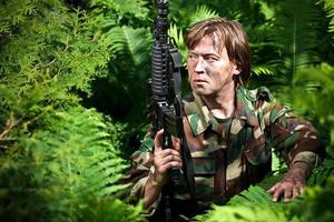 Soldat hält eine Waffe foto