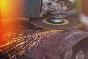 Arbeiter schleifen Stahlrohr mit Schleifer foto