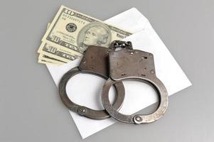 Handschellen und weißer Umschlag mit Geld auf grau foto