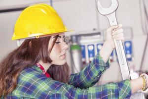 Porträt der jungen Metallarbeiterin, die mit Schraubenschlüssel beschäftigt ist