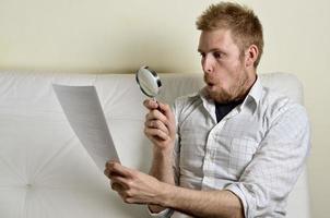 Porträt des hübschen jungen Mannes, der einen Vertrag liest foto