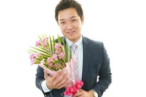 Mann hält Blumenstrauß