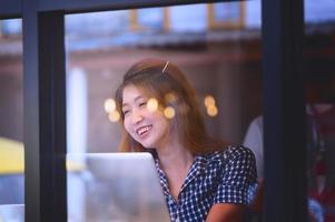 asiatische glückliche Frau, die am Entspannungstag am Stehtisch sitzt