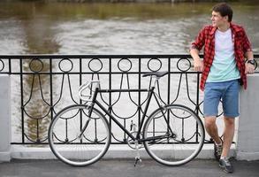 Hipster-Mann mit Fahrrad, das über Kai ruht foto