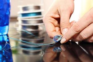 Frau gibt einen Juwelier bei der Arbeit an Schmuck foto