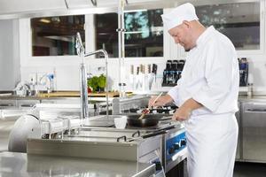 Koch mit Pinsel, um ein Gericht in der Küche zuzubereiten foto