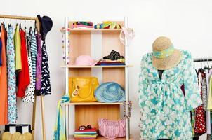 Kleiderschrank mit Sommerkleidung und Strandoutfit auf Schaufensterpuppe.