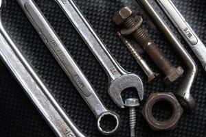 Diagonalmutternschlüssel an Kohlefaser, Muttern und Schrauben foto