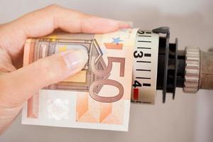 weiblicher Einstellthermostat mit Banknote foto