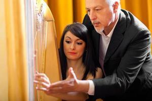 Frau lernt Harfe zu spielen foto