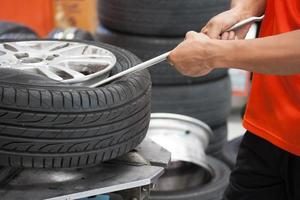 Mechaniker, der Autoreifennahaufnahme ändert foto