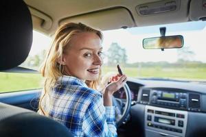 Frau, die Lippenstift in einem Auto während der Fahrt anwendet foto