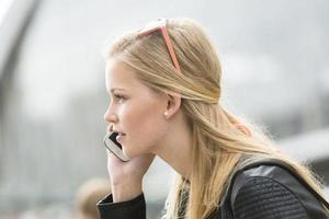Porträt der jungen Frau, die am Mobiltelefon spricht foto