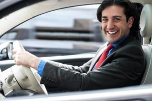 fröhlicher Mann, der sein neues luxuriöses Auto fährt foto