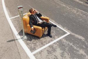 Geschäftsmann, der auf Sessel mitten auf der Straße sitzt