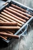 Rauch steigt von einer brennenden Zigarre auf hölzernen Humidor auf foto