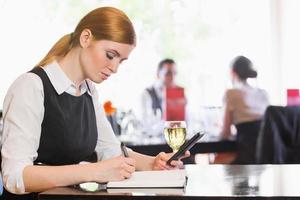 konzentrierte Geschäftsfrau hält Telefon beim Schreiben foto