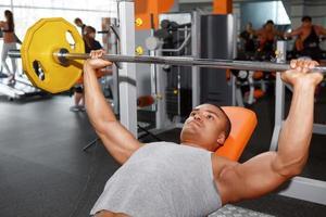 Liegender Mann, der Langhantel im Fitnessstudio hebt foto