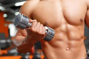 Kraftheber, der mit Hanteln im Fitnessstudio trainiert foto