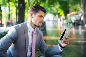 Geschäftsmann, der Zeitung draußen liest foto