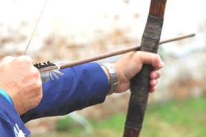 Geschäftsmann, der Bogen hält und zum Bogenschießenziel schießt