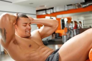 junger angenehmer Mann, der Bauchkrisen im Fitnessstudio tut foto