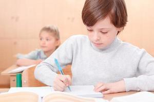 Schreiben eines kleinen Jungen während des Unterrichts