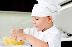 süßer kleiner Koch, der seine Küche probiert foto