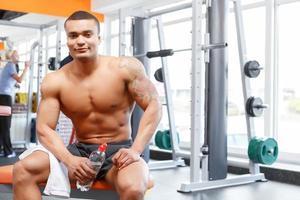 Mann sitzt mit Flasche und Handtuch im Fitnessstudio foto