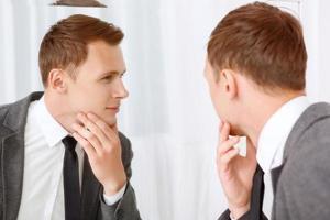 junger Mann, der seine Borstenhaare im Gesicht prüft foto
