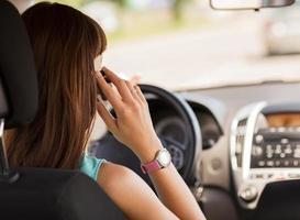 Frau, die Telefon benutzt, während sie das Auto fährt foto