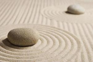 Kieselsteine sitzen in einem geharkten Zen-Garten