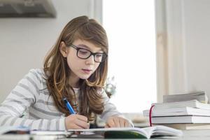 Teenager-Mädchen, das Hausaufgaben am Tisch macht