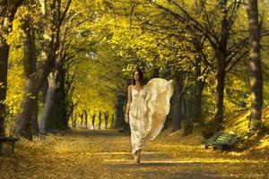 Frau geht im Herbstpark spazieren.