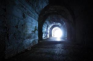 blau leuchtender Ausgang aus dem dunklen verlassenen Tunnel foto