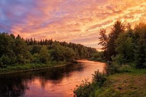 heller dramatischer Sonnenuntergang über Fluss mit Wald entlang des Flussufers foto