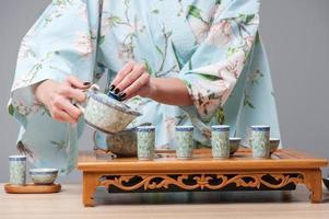 asiatische Schönheit, die sich für die Teezeremonie fertig macht