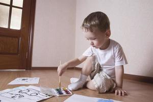Junge malt mit Aquarellen und Pinsel foto