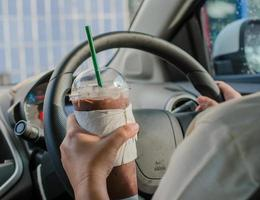 Fahrzeugkonzept - Mann, der Kaffee beim Fahren des Autos trinkt foto