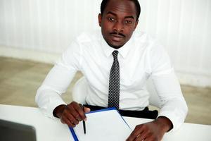 nachdenklicher afrikanischer Mann, der am Tisch sitzt foto