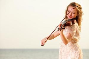 das blonde Mädchen mit einer Geige im Freien foto