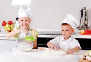 zwei glückliche kleine Kinder lernen backen