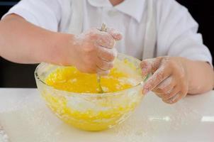 kleiner Junge, der Kuchenbestandteile mischt foto